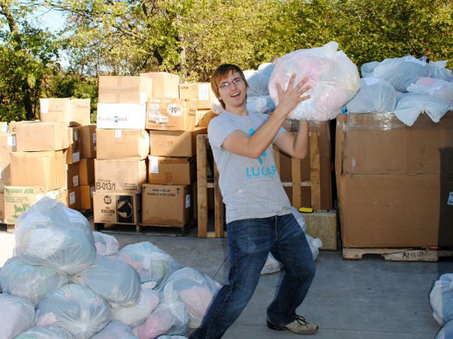 A LUCAP volunteer tosses a bag of donated clothes in Joplin, MO.